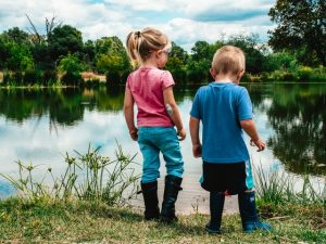 A boy and a girl next to a water pond