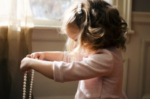 A girl holding a necklace